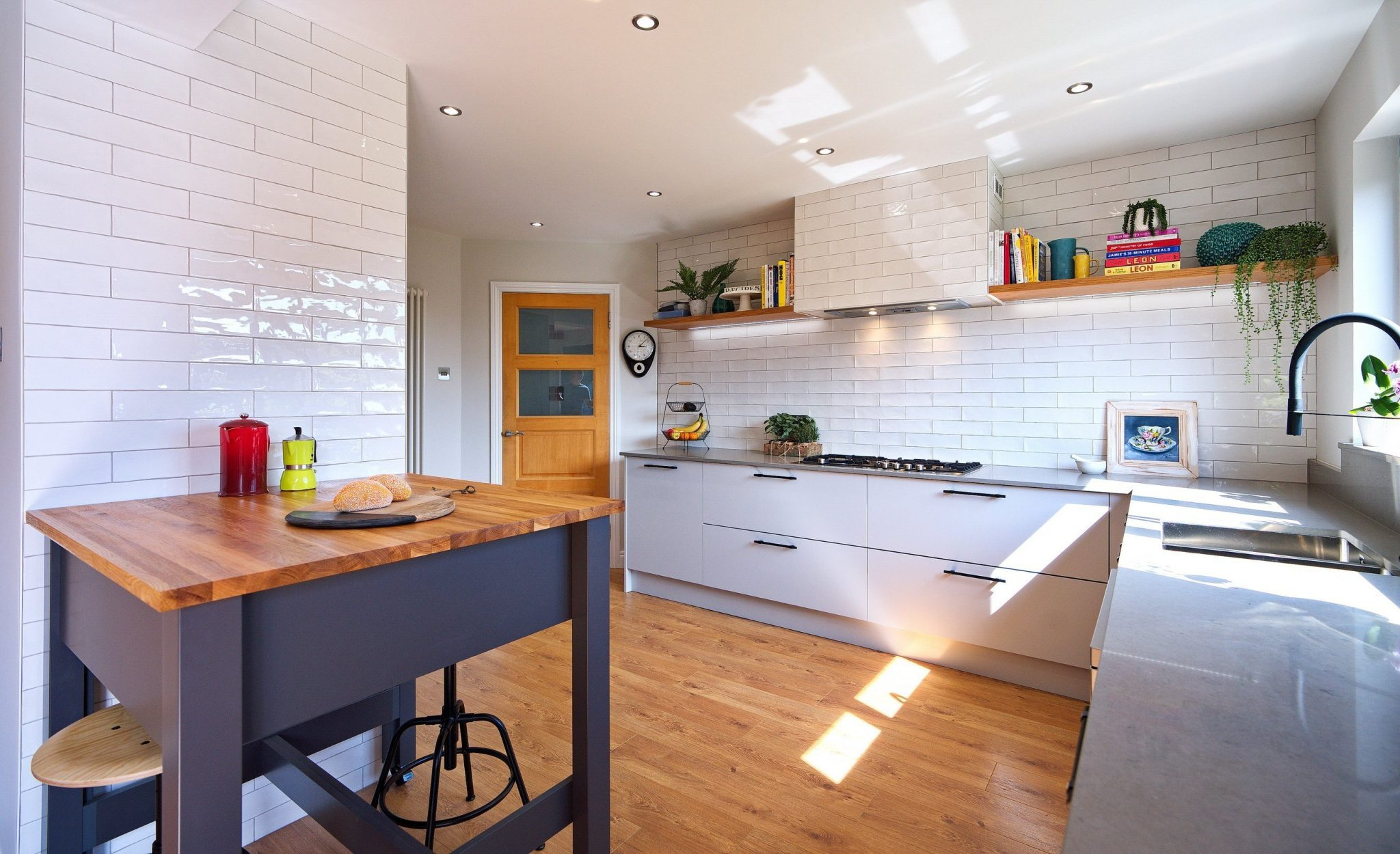 Modern kitchen with white tiles and grey worktops